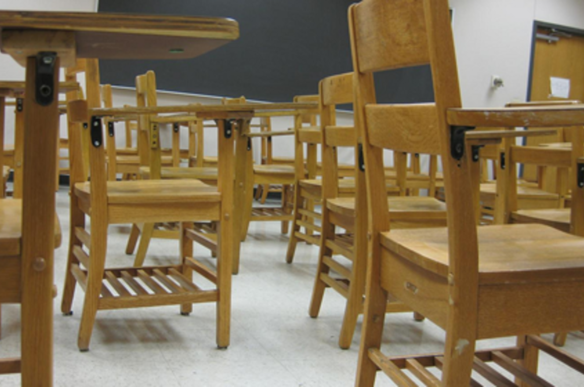 a bunch of desks in a classroom from a low vantage point