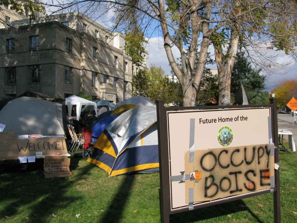 "a sign with a cardboard sign taped on top with spray painted ""occupy boise"" on it with tents in the background"