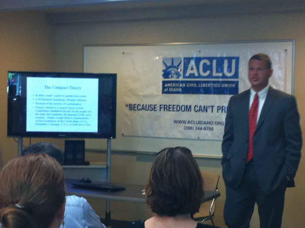 man in a suit standing in front of ACLU banner and talking to people in an audience.
